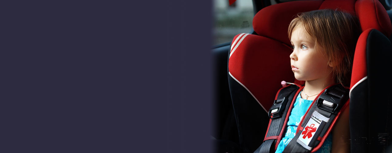 Photo of little girl in car seat wearing a Medipal Seatbelt ID