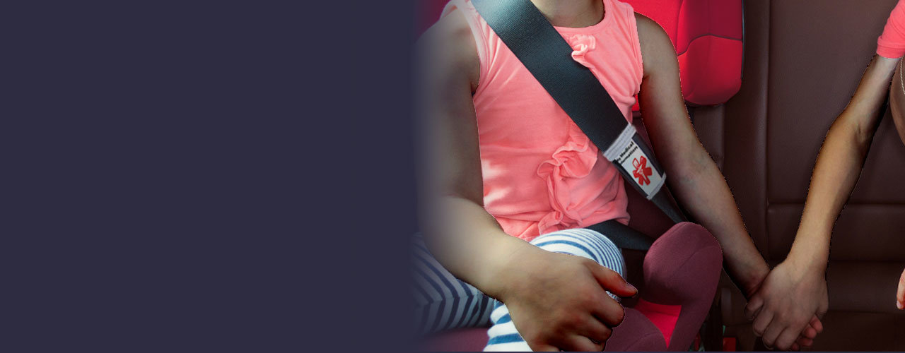 Sister and brother sitting in car seats with Medipal Seatbelt ID