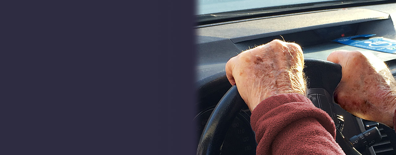 Photo of car steering wheel with elderly man driving.